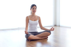 Beautiful young woman doing yoga exercises at home. Stock Image