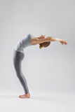 Beautiful young woman doing yoga on a gray studio background Royalty Free Stock Images