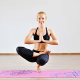 Beautiful young woman doing yoga on one leg position Stock Images
