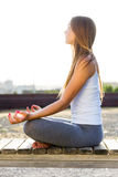 Beautiful young woman doing yoga in the street. Portrait of beautiful young woman doing yoga in the street Stock Image