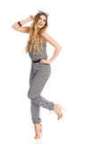 Carefree Young Woman In Jumpsuit Is Standing On One Leg And Smiling Royalty Free Stock Images