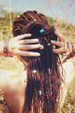 Beautiful young woman with dreadlocks hairstyle gathered in a ponytail, decorated assorted beads Royalty Free Stock Photo