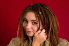 Beautiful young woman with dreadlocks on a red Royalty Free Stock Photos