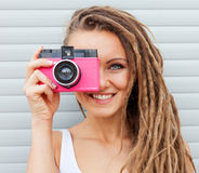 Beautiful young woman with dreadlocks taking photos with vintage pink retro film camera Stock Images