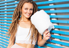 Beautiful young woman with dreads posing near blue plank wall with cotton candy summer warm evening. Look at camera Stock Image