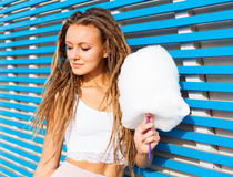 Beautiful young woman with dreads posing near blue plank wall with cotton candy summer warm evening Royalty Free Stock Photos