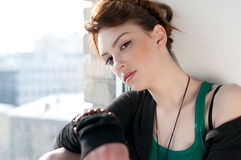 Beautiful young woman dreaming on window Royalty Free Stock Photography