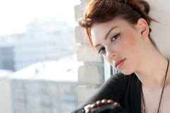 Beautiful young woman dreaming on window Stock Photos