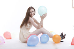 Beautiful young woman in dress on floor with balloons against white background Royalty Free Stock Images
