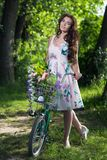 Beautiful Young Woman in a Dress and Hat on a Bicycle on the Nat Royalty Free Stock Photos