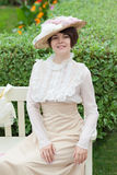 Beautiful young woman in dress and hat portrait in retro style. Vogue dressing in vintage Stock Image