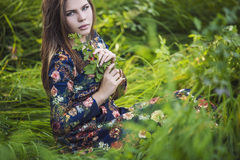 Beautiful young woman in a dress of nature with a plant in hand Royalty Free Stock Photography