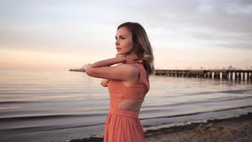 Beautiful young woman in a dress posing along the coast smiling at sunset near the sea stock video