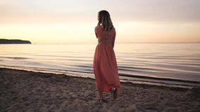 Beautiful young woman in a dress posing along the coast smiling at sunset near the sea stock video footage