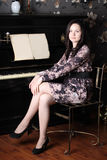 Beautiful young woman in dress sit at black old piano Stock Images