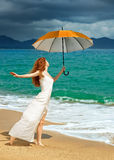 Beautiful young woman in dress standing on the beach with an umbrella before the rain. stock photography