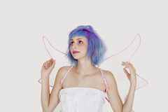 Beautiful young woman dressed as angel with dyed hair looking up against gray background Stock Photography