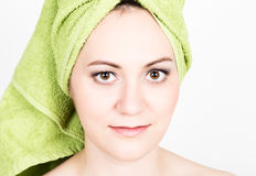 Beautiful Young woman dressed in a bath towel makes a cosmetic mask on the face. beauty industry and home skin care Royalty Free Stock Image