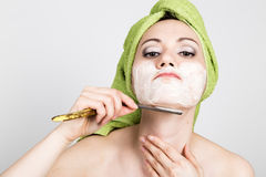 Beautiful Young woman dressed in a bath towel shaves with a straight razor. beauty industry and home skin care concept Royalty Free Stock Image