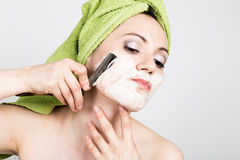 Beautiful Young woman dressed in a bath towel shaves with a straight razor. beauty industry and home skin care concept Royalty Free Stock Images