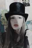 Beautiful young woman dressed in black high hat Royalty Free Stock Photo