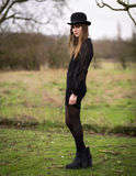 Beautiful Young Woman Dressed In Black Wearing Bowler Hat. Portrait of a beautiful young woman wearing a black dress, nylons, boots and a bowler hat standing in stock image