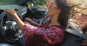 Beautiful young woman dressed in boho style driving her friends in convertible. Beautiful young woman smiling and enjoying driving her friends in convertible stock video footage