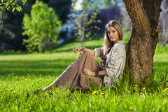 Beautiful young woman dressed in boho style sitting on green gra Stock Photo