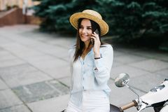 Beautiful young woman dressed casual sitting on scooter and talking on phone. Girl sitting on the bike and using Cellular smartpho Royalty Free Stock Photography
