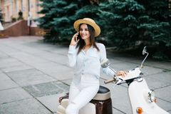 Beautiful young woman dressed casual sitting on scooter and talking on phone. Girl sitting on the bike and using Cellular smartpho stock photo