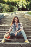 Beautiful young woman dressed in jeans posing on a concrete stai Royalty Free Stock Photo