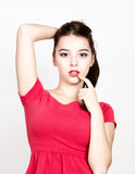 Beautiful young woman dressed in a red dress, raised finger to lips. studio shot Stock Images