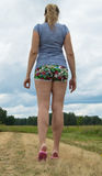 Beautiful young woman dressed in shorts and a t-shirt stands on the road against the sky and grass.  stock photo