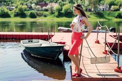 A beautiful young woman dressed stand on the pier. Staring into the distance Royalty Free Stock Photo