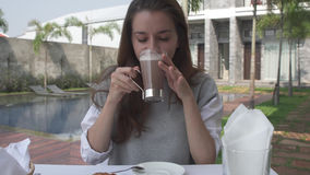 Beautiful young woman drink cacao during morning breakfast on luxury villa. Female drinking hot chocolate and looking to camera. 4K royalty free stock images