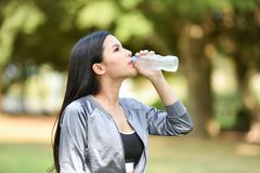 Drink water after sport. Beautiful young woman drink water after sport - outdoors training girl morning fitness exercises Royalty Free Stock Image