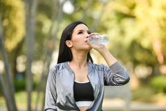 Drink water after sport. Beautiful young woman drink water after sport - outdoors training girl morning fitness exercises Royalty Free Stock Photo