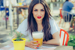 Beautiful young woman drinking beer and enjoying summer day Stock Photography