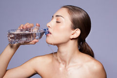 Beautiful young woman drinking from a bottle of water Stock Image
