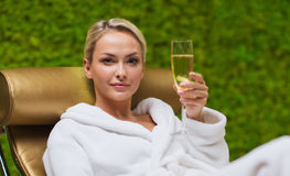 Beautiful young woman drinking champagne at spa Stock Images