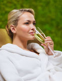 Beautiful young woman drinking champagne at spa Royalty Free Stock Photos