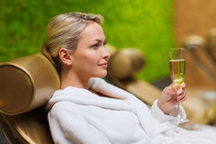 Beautiful young woman drinking champagne at spa Stock Photography