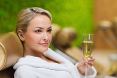 Beautiful young woman drinking champagne at spa Stock Photos