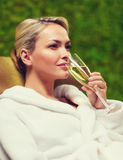 Beautiful young woman drinking champagne at spa Royalty Free Stock Images