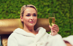 Beautiful young woman drinking champagne at spa Stock Photo