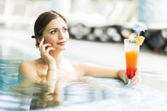 Beautiful young woman drinking a cocktail while in the swimming Royalty Free Stock Photography