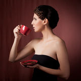 Beautiful young woman drinking coffee. Against dark background Stock Image
