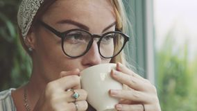 Beautiful young woman drinking coffee in cafe. Girl dreaming. Female wearing glasses. stock video