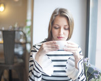 Beautiful young woman drinking coffee in cafe Royalty Free Stock Photo