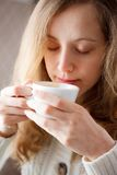 Beautiful young woman drinking coffee. Cup of hot beverage Royalty Free Stock Photos